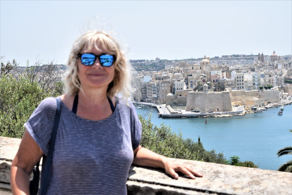 Sue in Valletta, behind is the view across the Grand Harbour to Vittorioso