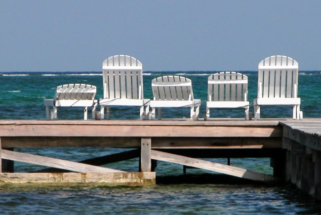 A row of white sunbeds facing out to sea Ambergris, Caye, Belize