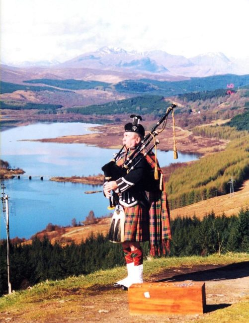 A piper in a kilt playing above Loch Lomond