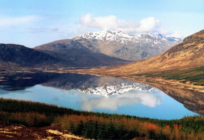 Snow dusted peaks reflected in a loch north west Scotland