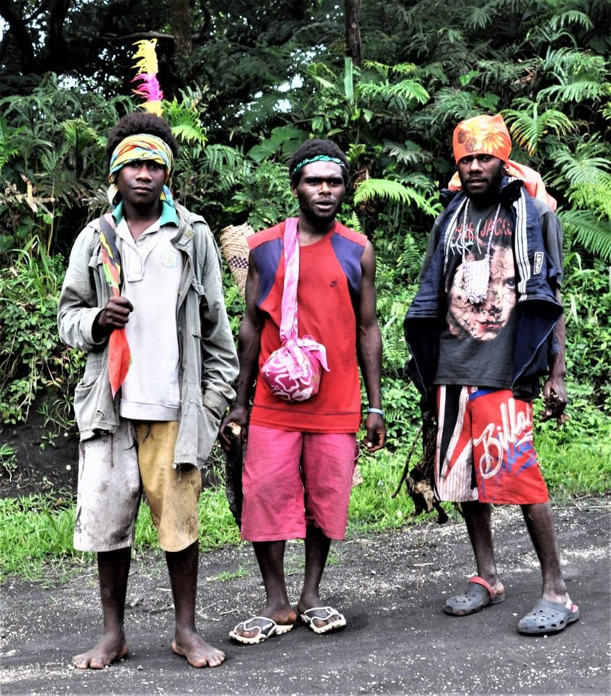 Three young men, last night revellers with feathers and headscarves Vanuatu