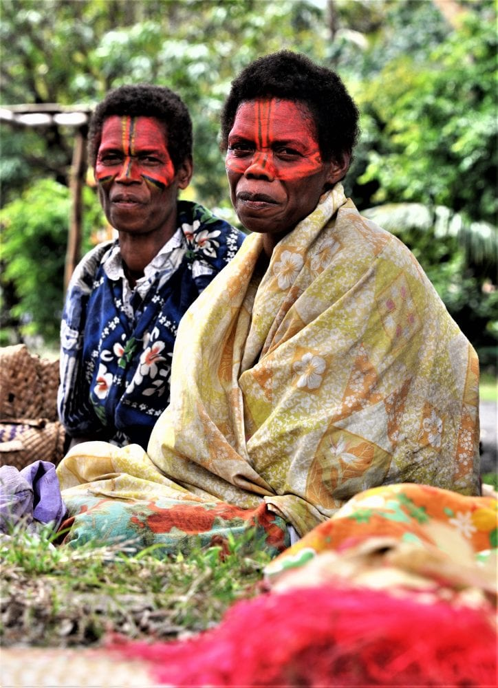 Two suffering last night revellers with red face paint, Vanuatu