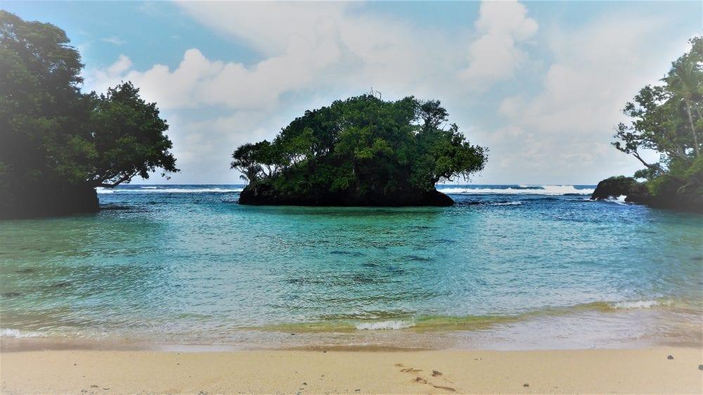 A small motu behind a miniature blue lagoon in Samoa