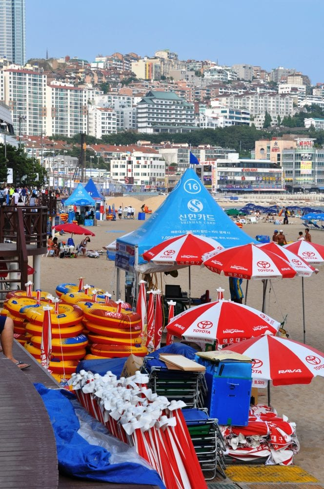 Bright umbrellas and inflatables stacked on the beach at Busan, South Korea