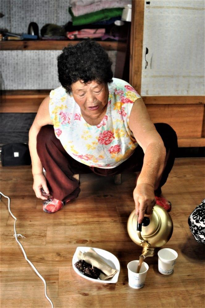 A squatting Korean lady pours millet tea on Jeju