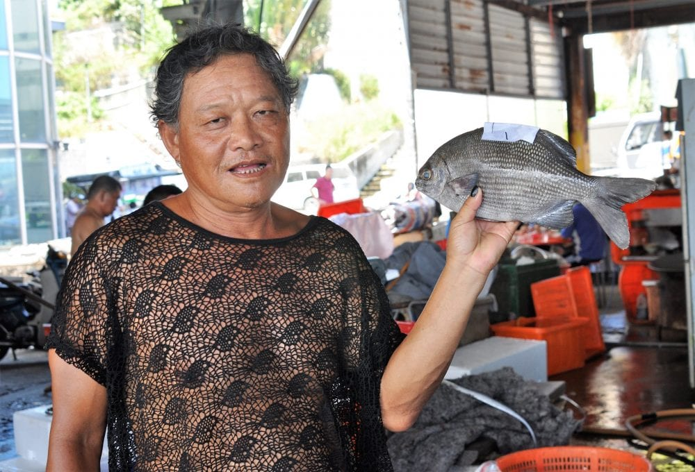 Man holds up a fish at the market