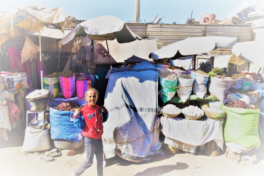A young girl in front of a market stall in Eritrea