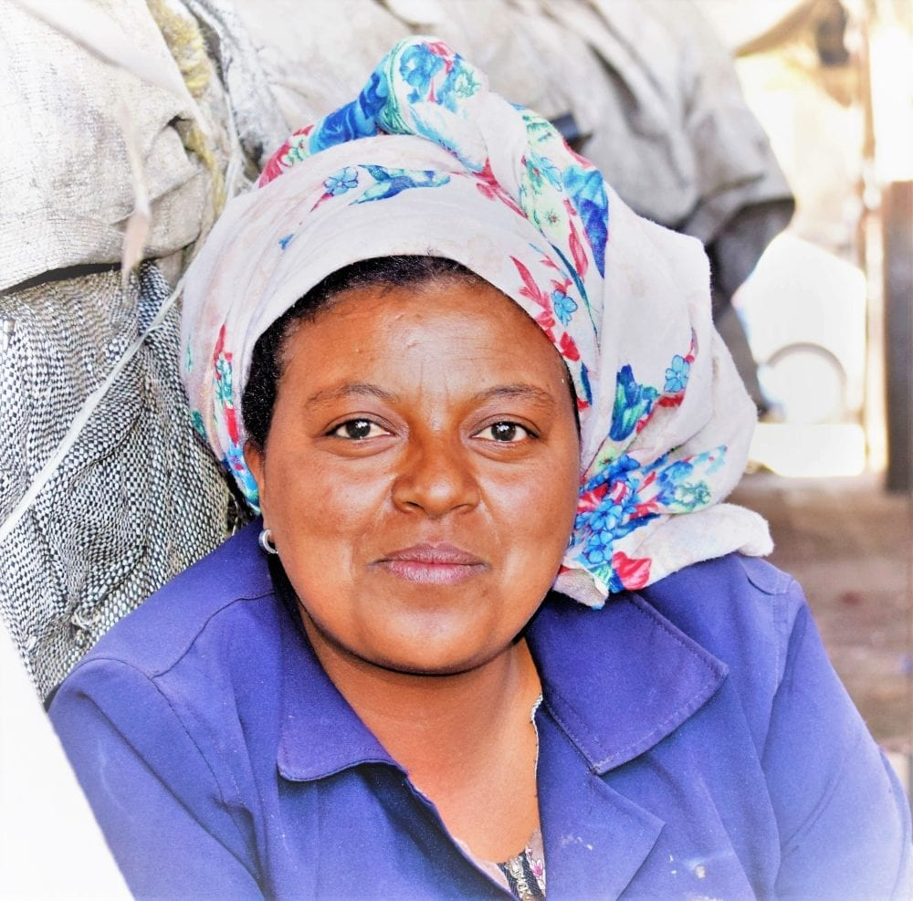 A portrait of an Eritrean lady in a white patterned headscarf