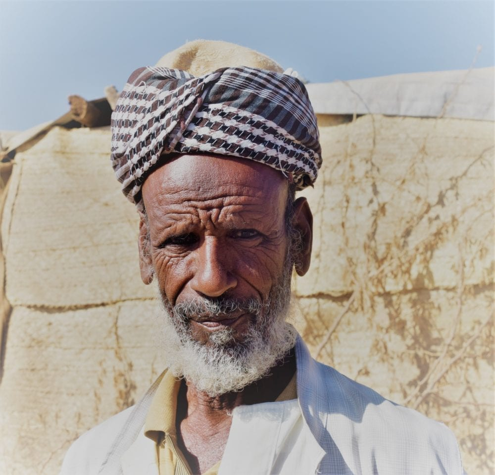 A portrait of a man with white beard and checked turban in Eritrea