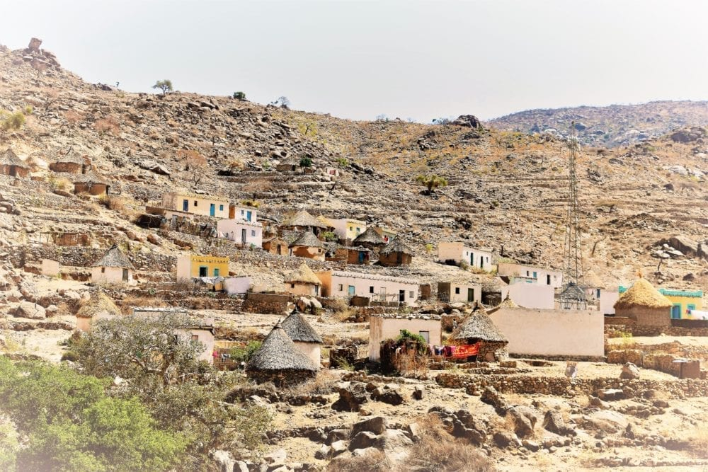 A vilalge with small cuboid houses and round huts strung up a hillside in Eritrea