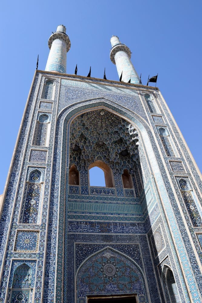 A view of a tower on a blue and white mosque in Yadz, Iran looking up