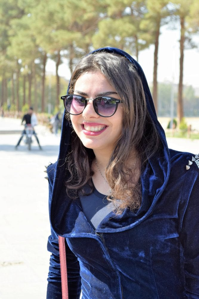 A headshot of an Iranian lady in a velvet hooded dress