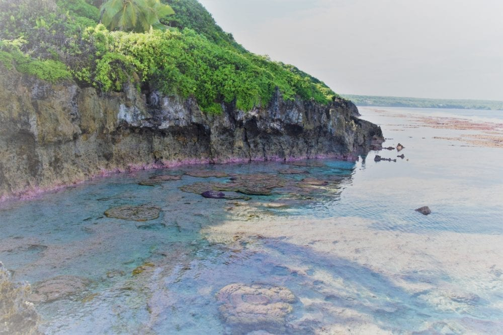 The pink coloured rock and turquoise water of the bay at Aikaivai Cave Niue