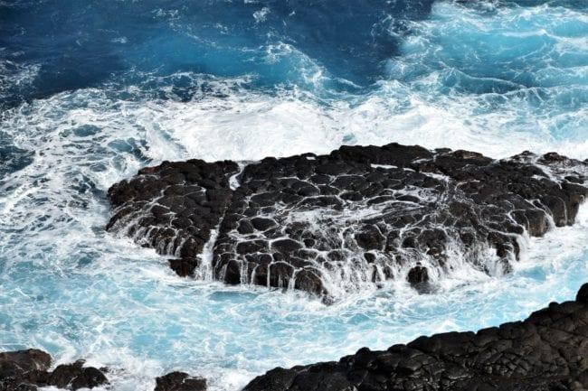 The sea boils around basalt rocks at Crystal Pool