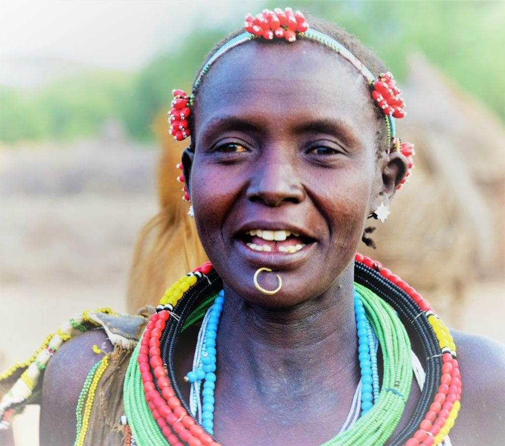 A portrait of a lady with decorated headband, lip piercing and multiple beaded necklaces in South Sudan