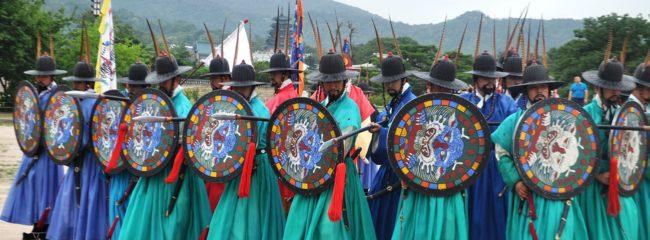 Turquoise hanbok wearing men wielding shields at the changing of the guard, Gyeongbokgung Palace, Seoul