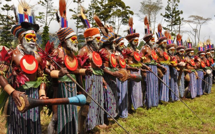A tribal grup at the SingSing Festival, wearing blue and white sarongs and red discs on their chests, PNG