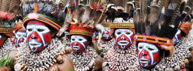 Close up of a female group at the SingSing festival- they have red and white facepaint, huge shell necklaces and enormous feathered headdresses, PNG