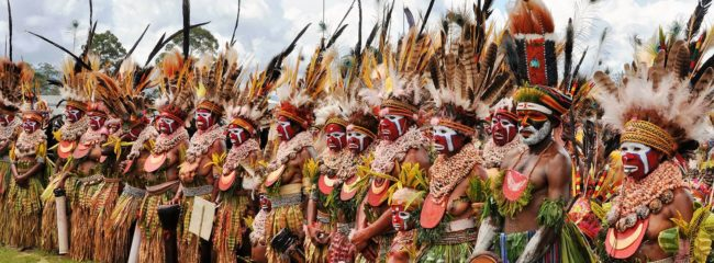 A female group at the SingSing festival- they have red and white facepaint, huge shell necklaces and enormous feathered headdresses, PNG