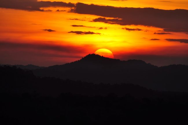 The sun sets in a huge fiery ball over the rainforest at Sepik, PNG