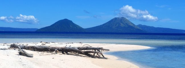 A view across white sand of a coral island to two volcanoes at Rabaul