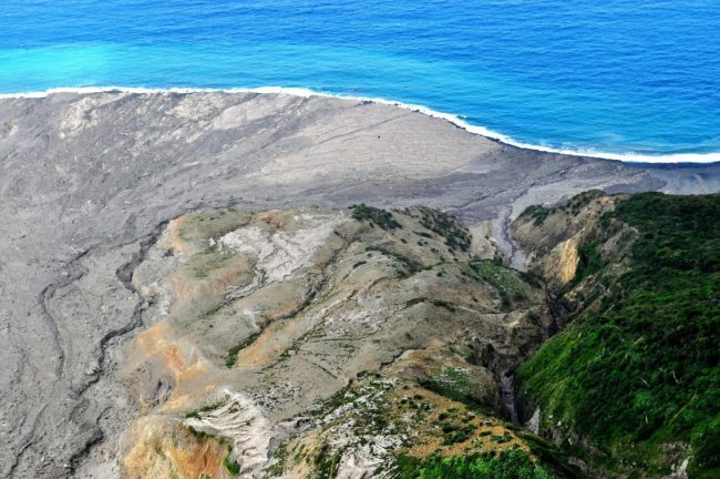 A turquoise sea on the coastline of Montserrat, where lava has flowed into the sea