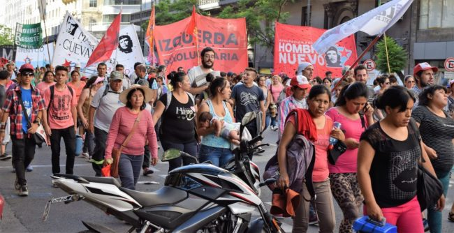Protestors wearing red and carrying red banners march down the Avenida del Mayo, Buenos Aires