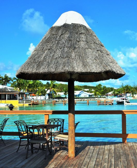 Thatched umbrella and table by the blue waters of the harbour, Exumas