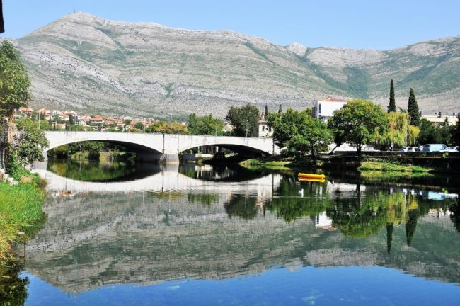 A bridge framed by mountains reflected in the river, Bosnia