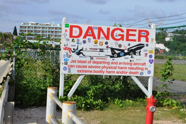 A danger sign at the end of the airport runway at Maho Beach