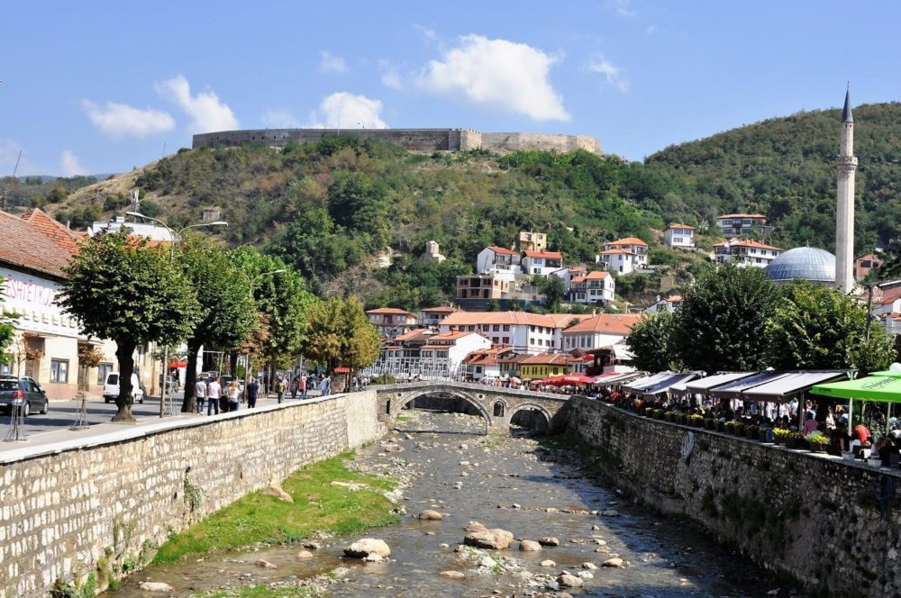 A view up the river to a stone bridge, lined with market stalls in Prizren, Kosovo