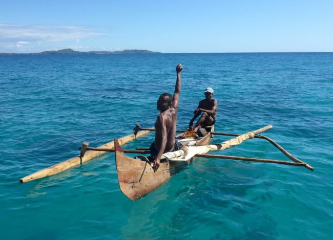 Two fishermen in anrrow wooden canoe out at sea, one raising his arm in salute