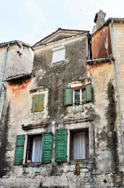 Green shuttered windows on a dilapidated house in Kotor, Montenegro