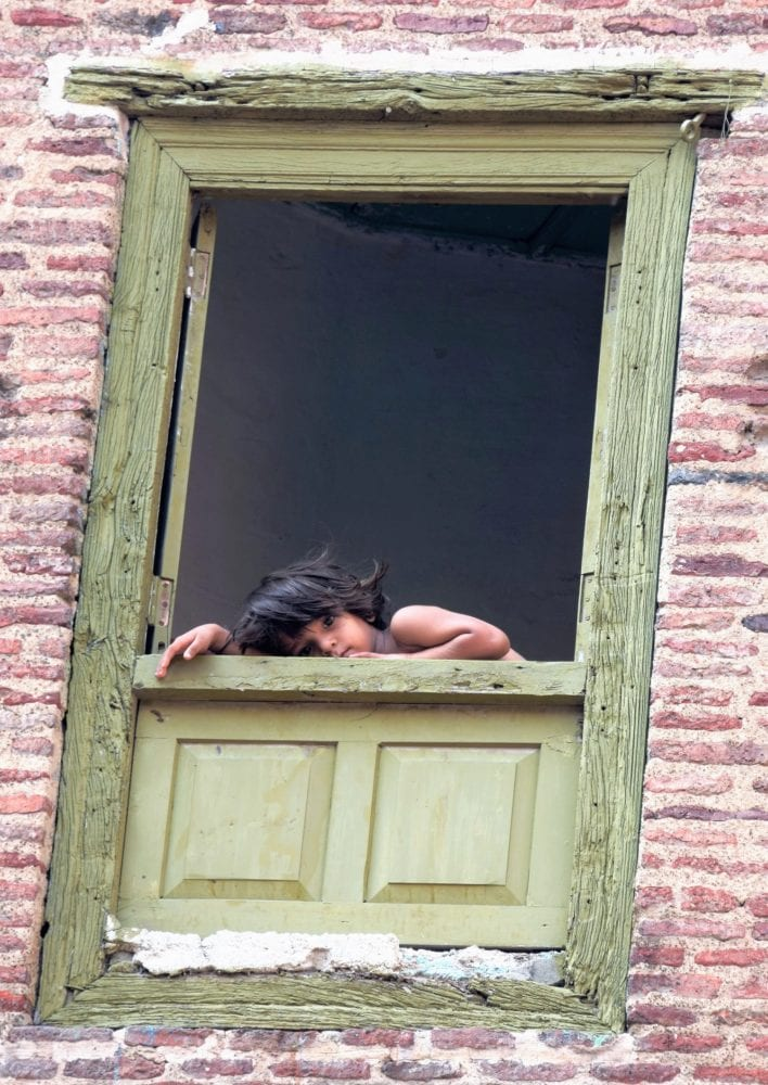 A child leans on the ledge of a green angled window