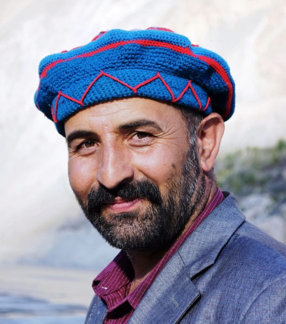 A headshot of a smiling Pakistani man in blue and red knitted beret