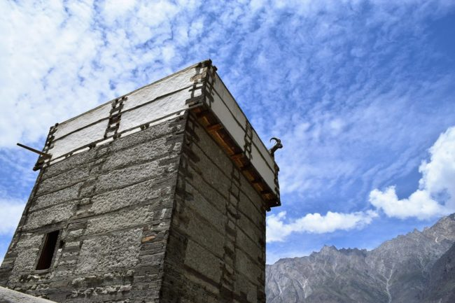A goat figure peeping over the tower of the fort at Altit taken from below framed against a blue and cloud sky, Pakistan