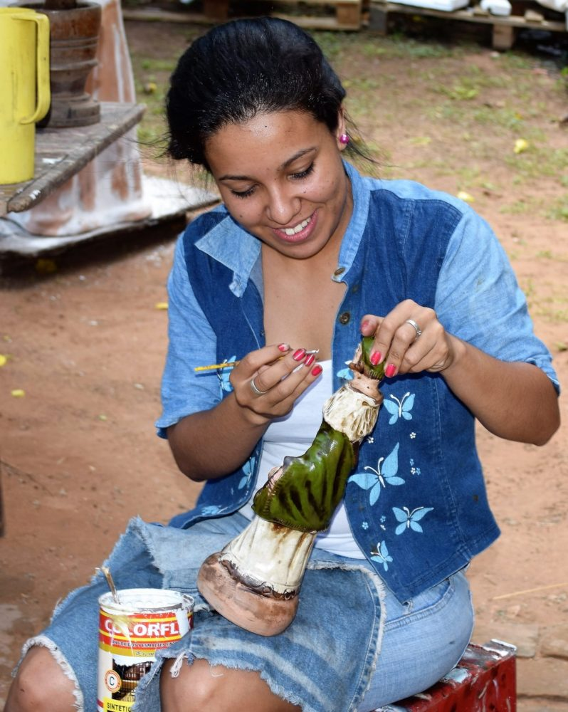 A woman paints pottery at Aregua