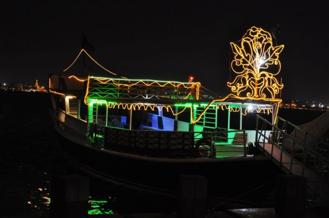 An illuminated boat in the dhow harbour at Doha, Qatar