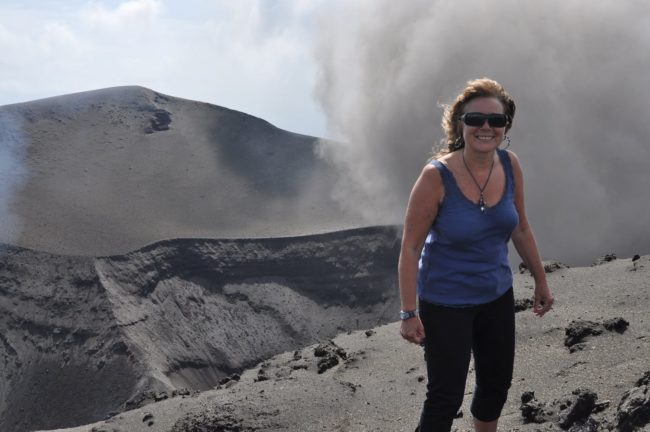 Sue in the gust on the edge of Mount Yasur crater, smoke billowing from the crater behind, Vanuatu