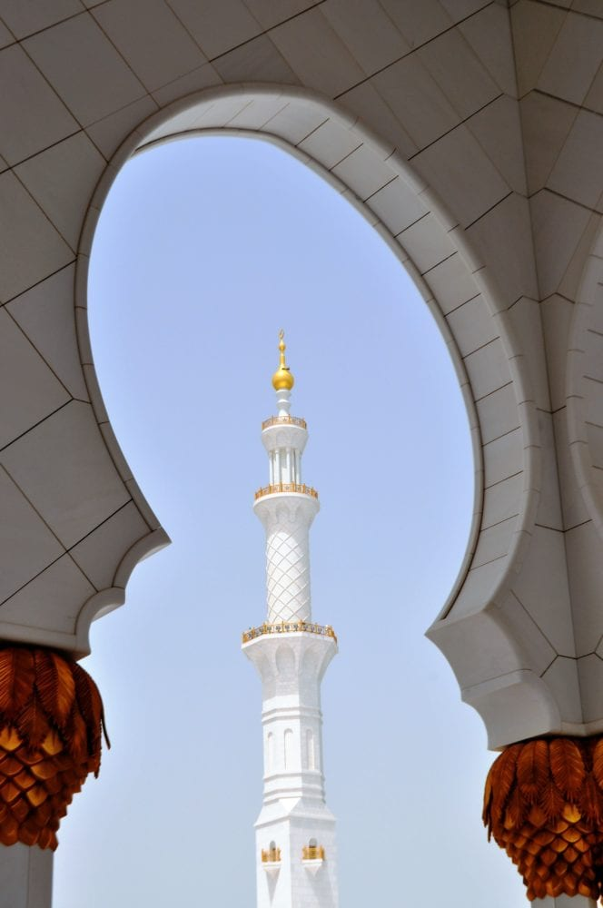 A slim white and gold minaret at the Sheikh Zayed Grand Mosque, framed by an arch