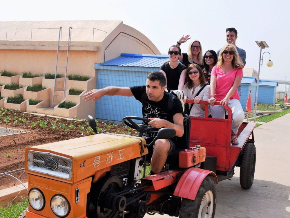 Some of the tour group on a tractor 'driven' by Giorgio at the cooperative farm in Pyongyang
