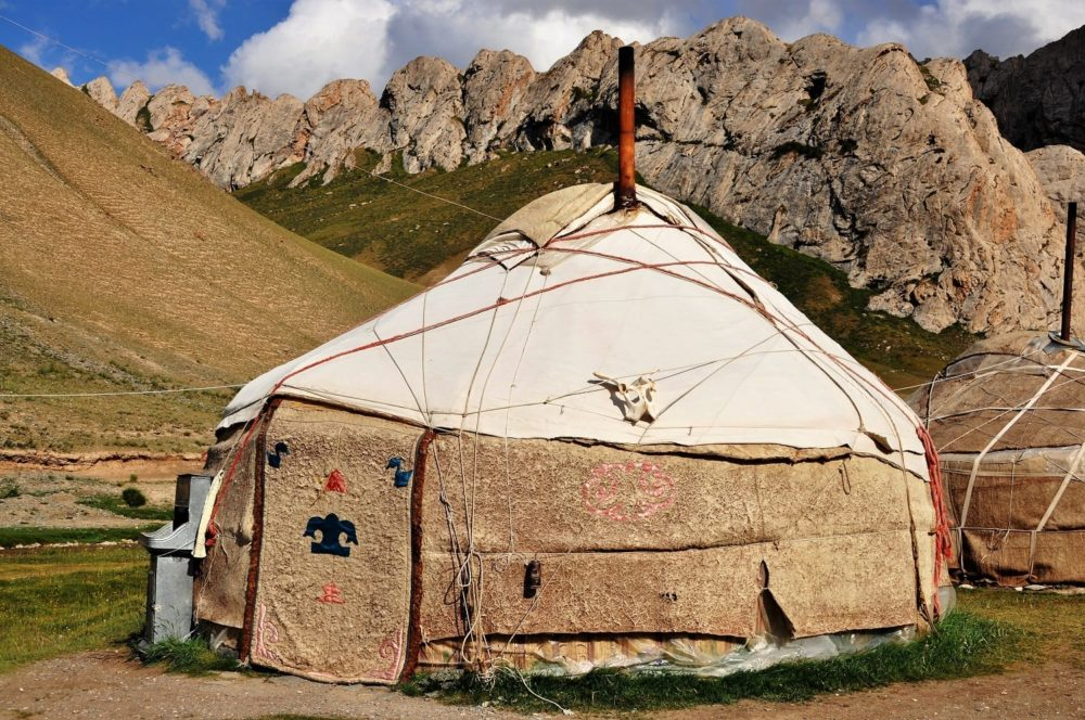 A yurt framed by tooth shaped mountains at Tash Rabat, Kyrgyzstan