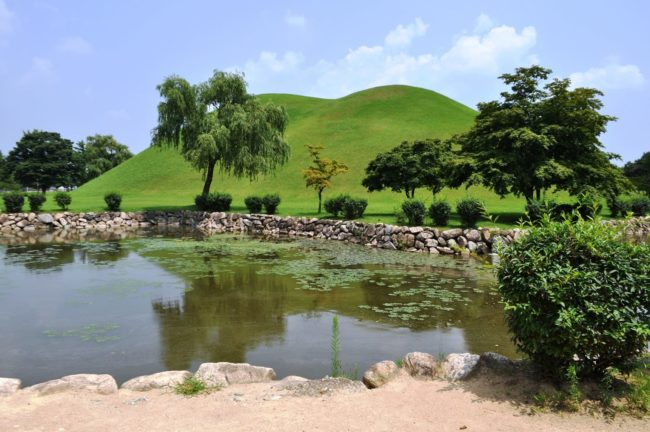Domed Silla burial grounds reflected in a lake Gyeongju , South Korea
