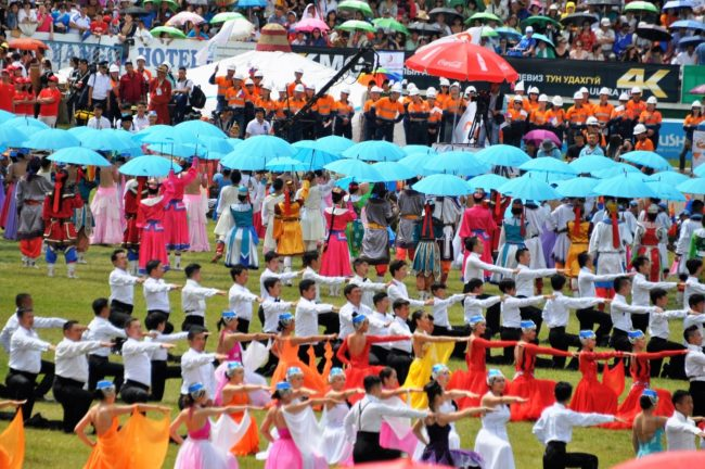 Ceremonial dancing and marching with parasols Naadam games. Mongolia