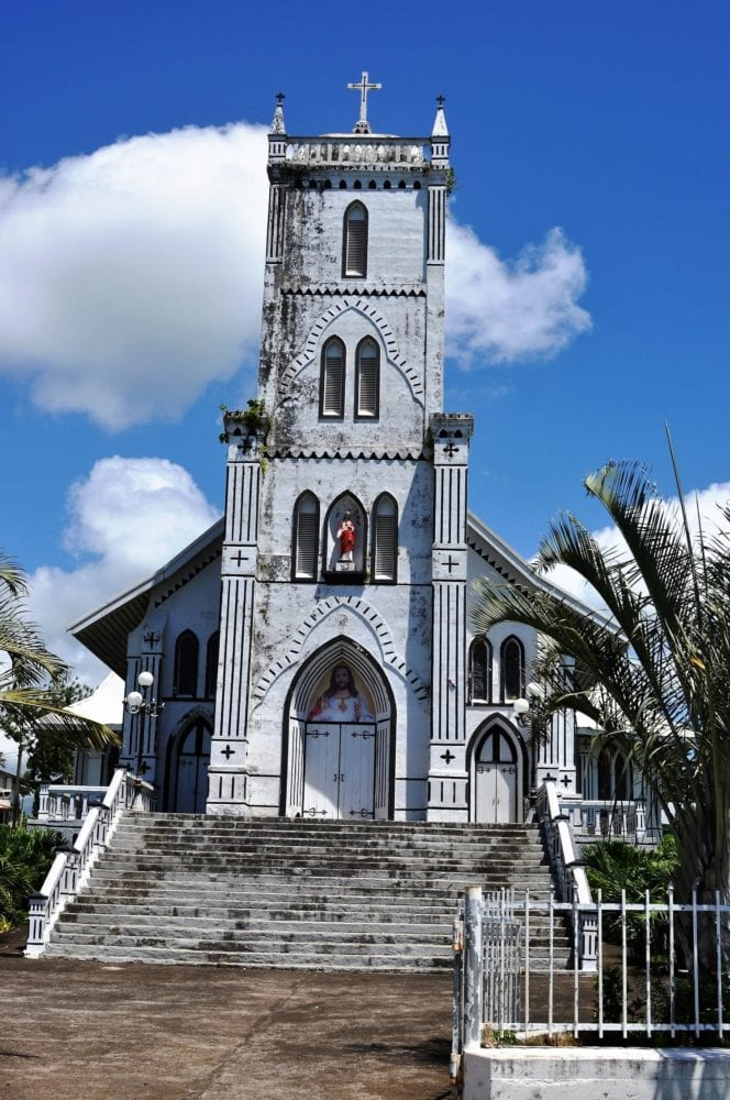 The tall white tower of a church in Samoa seen from the front