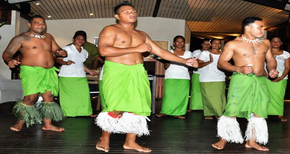 Polynesian dancers in green sarongs and grass shin decorations