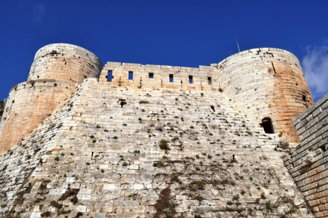 A close up of two turrets and the solid walls of the Krak des Chevaliers castle