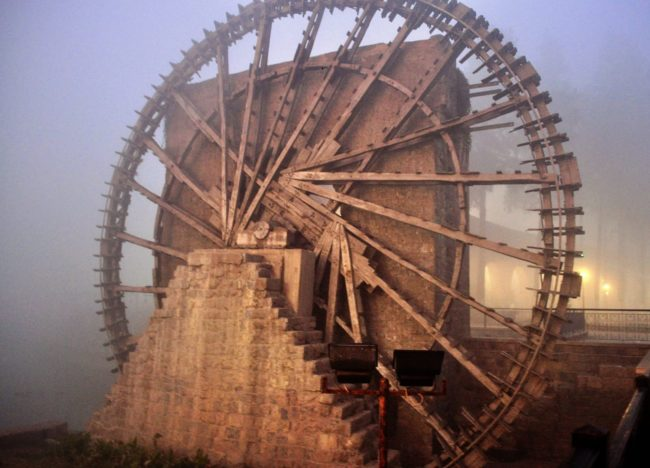 A huge noria (water wheel) turning in the mist at Homs, Syria