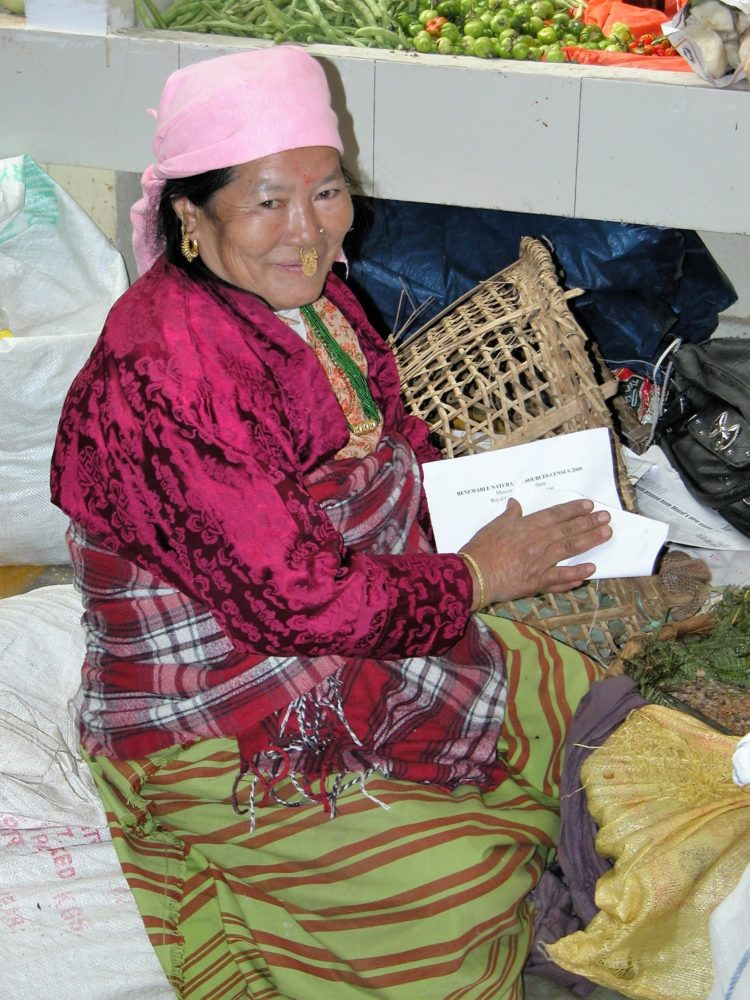 A Bhutanese lady with a nose piercing seated at a market