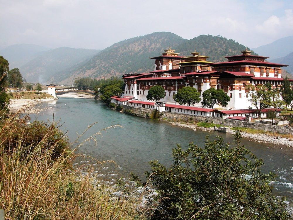 A view of Punakha Dzong and its ancient wooden bridge across the river in Bhutan